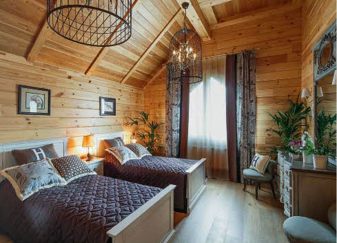В большой гостевой спальне размещены две широкие кровати. Люстры, помещенные в оболочку птичьих клеток, вносят в развитие интерьера интригу, напоминая о сказках, истории и причудливых переплетениях мотивов разных культур. Они гармонично работают в тандеме с композицией из двух зеркал — большого квадратного и маленького круглого