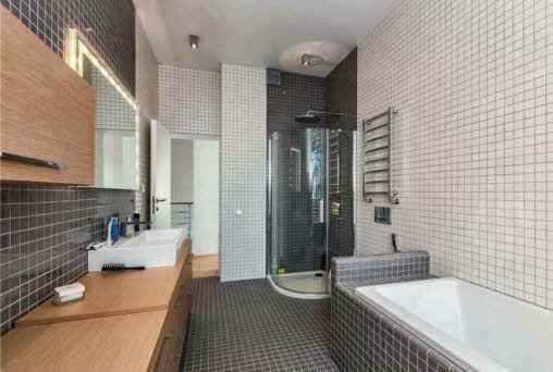 Стены и пол ванной комнаты, расположенной между спальнями на втором этаже, облицованы мелкоформатной квадратной плиткой двух оттенков. Лаконичности в дизайне придерживались и здесь — строгие деревянные фасады мебели снабжены металлической фурнитурой, раковина подобрана прямоугольной формы, чаша ванны встроена в подиум и облицована плиткой. Из комнаты предусмотрен выход на балкон