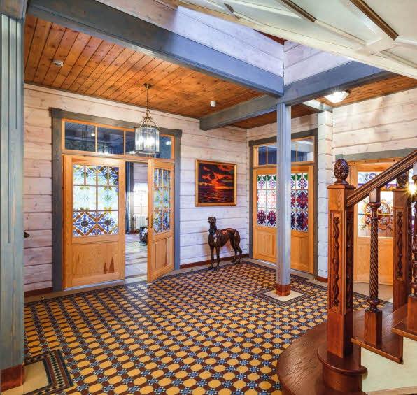 Витражи на дверях выполнены в технике росписи по стеклу с мотивами, перекликающимися с орнаментальными узорами облицовки каминного портала. Четкая геометрия керамической плитки, которой выложен пол, визуально контрастирует с деревянными поверхностями лестничного холла первого этажа, выступающими в качестве натурального оттеняющего фона