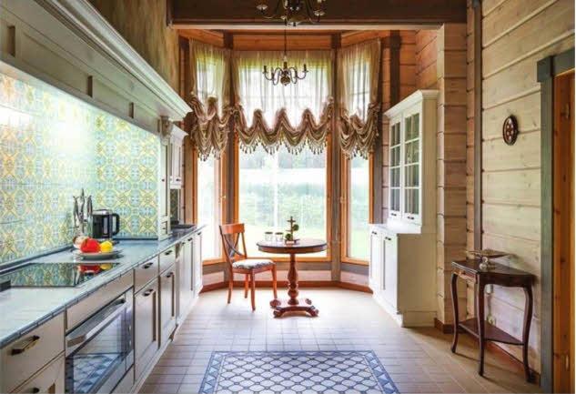 Элегантная респектабельность интерьера кухни основана на сочетании высокой функциональности помещения с тщательно продуманными, необходимыми техническими и эстетическими элементами. Серо-голубая плитка столешницы оттеняет «фартук» над рабочей зоной, выложенной керамической плиткой с таким же ковровым узором, что представлен в облицовке камина
