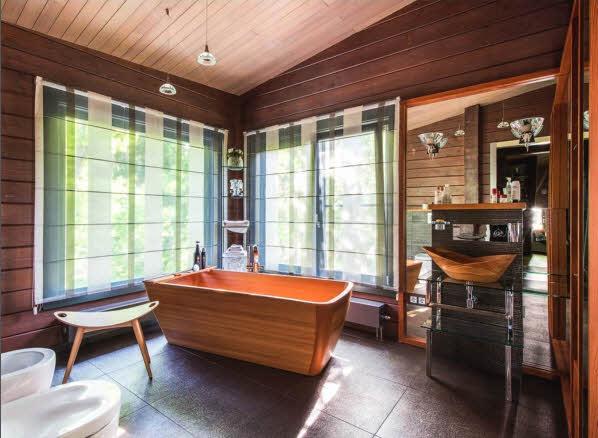 Благодаря хорошему вкусу и слаженному взаимодействию владельцев дома с авторами проекта и в архитектуре, и в интерьерах удалось воплотить много неординарных идей. Композиционным центром ванной комнаты хозяйки стала деревянная ванна, размещенная вблизи окон. Зеркальный стеллаж, обрамляющий угол комнаты, зрительно расширяет пространство