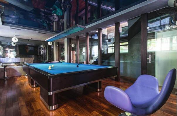 На цокольном этаже находятся просторная комната отдыха с бильярдным столом и зал плавательного бассейна. В дизайне обеих зон использован интересный прием — отделка масти стен зеркальной мозаикой, растворяющей границы пространства и создающей ощущение слияния с окружающей средой. Данный эффект усиливают синие глянцевые натяжные потолки