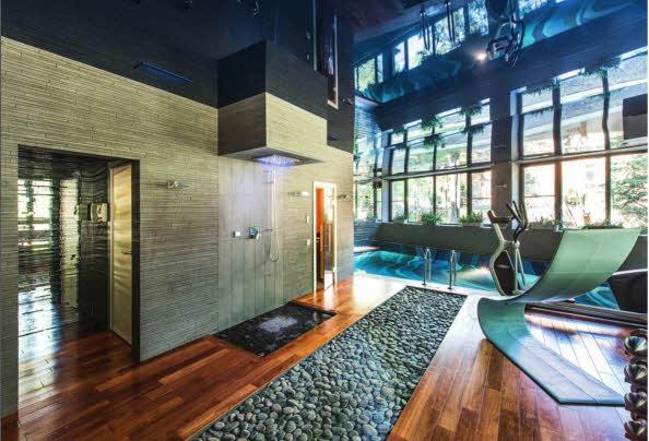 В дизайн загородной резиденции активно включен камень с естественной фактурой: речная галька — в зале бассейна, облицовка колонн — в беседке