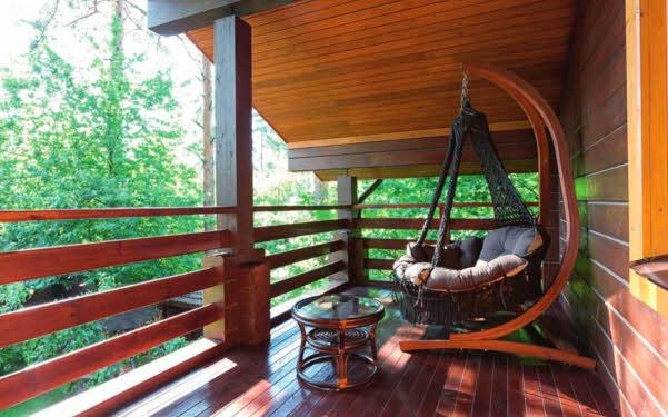 Широкий балкон при главной спальне со стильной летней мебелью — уютный уголок для отдыха и чтения. Стилизованный под старину комод и изящная хрустальная люстра вносят ноты роскоши в оформление строгой неоклассической спальни.