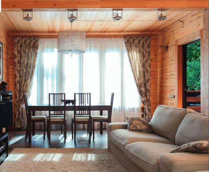 Столовая с выходом на террасу органично продолжает пространство гостиной. Условной границей между двумя функциональными зонами служит линия потолочных светильников-спотов современного дизайна. Расположение обеденной зоны с элегантной столовой мебелью у большого окна акцентировано с помощью люстры с хрустальными подвесками