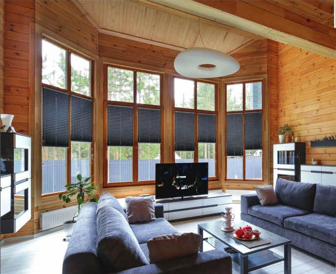Большая гостиная наполнена мягким дневным светом в любую погоду — высокие панорамные окна объединяют интерьер с природой. Напольное покрытие из светлого ламината (Quick-Step, Бельгия) создает спокойный фон для двух лаконичных диванов. Абстрактный геометрический светильник от Globo Lighting (Австрия), свободно парящий под потолком, вносит завершающий штрих в образ помещения