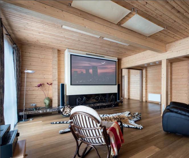 В гостиной камин композиционно объединен с домашним кинотеатром, широкий экран которого опускается с потолка перед просмотром фильмов. Деревянное кресло-качалка и тигровая шкура на полу придают интерьеру особенный колорит.