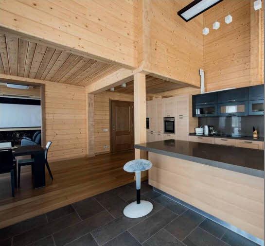 Кухню с современной лаконичной мебелью дополняет элегантная зона бара со стойкой из темного натурального мрамора