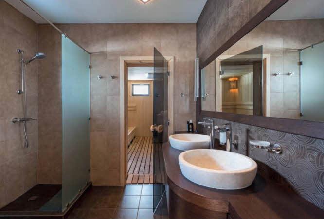 Ванная комната при главной спальне продолжена сауной — вместе они образуют комфортный и роскошный спа-центр в загородном доме