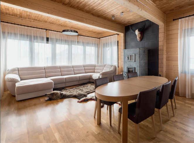 Для приема гостей хорошо подходит комната отдыха, расположенная в одном из боковых флигелей особняка. Атмосферу уюта в ней создает каминная печь из талькохлорита, акцентированная отделкой торцевой стены темно-серой керамической плиткой. Строгую ортогональную геометрию интерьера смягчают плавные округлые формы обеденного стола и дивана
