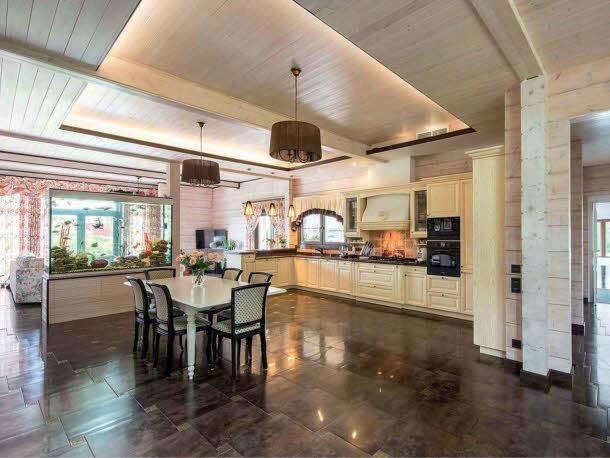 В большом едином пространстве гостиной-столовой уложено напольное покрытие из полированного темно-коричневого керамического гранита, отражающее свет. Вместе со светлыми выбеленными стенами оно усиливает эффект воздуха и простора. Зона кухни с Г-образной расстановкой мебели и встроенной современной бытовой техникой оформлена в стиле кантри