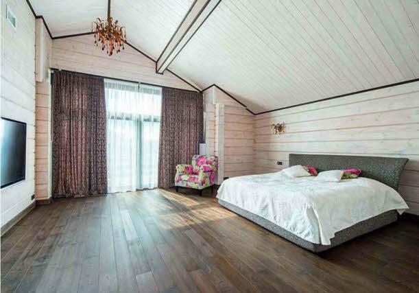 Масштаб хозяйской спальни на втором этаже подчеркивает большое окно, начинающееся от уровня пола и задрапированное легкими струящимися шторами.