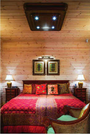 Почти повсюду в доме сосновый брус сохранил свой естественный оттенок, за исключением спальни с ярким текстилем, где стены были слегка выбелены