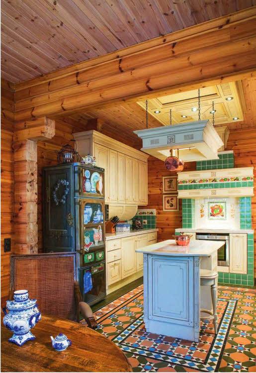Варочная панель и духовой шкаф в кухне встроены в специальную конструкцию, стилизованную под изразцовую печь. Современный холодильник, расписанный с помощью аэрографа, стал похож на старинный шкаф для хранения посуды и запасов провизии. Расположение кухонного «острова» композиционно поддержано декоративным элементом, подвешенным к потолку на цепях