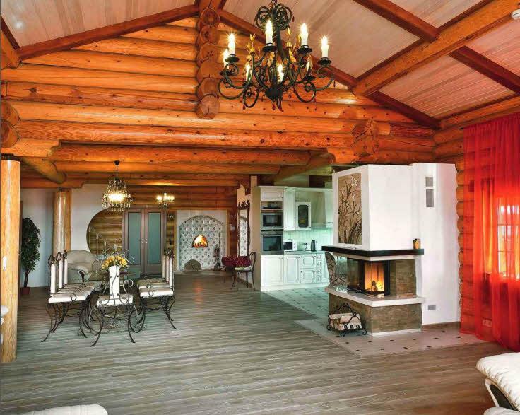 В интерьере гостиной теплое обаяние деревянного дома сочетается с элегантностью классики — мягкая мебель с кожаной обивкой цвета слоновой кости и кованая люстра расставляют в пространстве нужные акценты