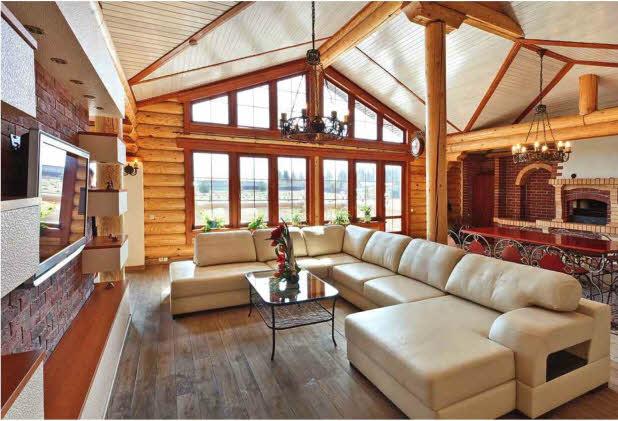 Вторая, гостевая, часть дома с барбекю, бильярдной и кальянной выглядит современной благодаря панорамному остеклению фасада и организации пространства. Диван с низкой спинкой делит интерьер на зоны