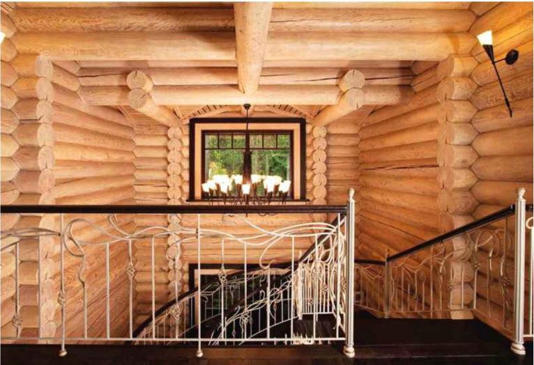 Деревянная лестница с коваными ограждениями, соединяющая этажи дома, изготовлена по эскизам архитектора. Массивные бревенчатые стены обработаны белым прозрачным воском, сохраняющим естественную текстуру древесины.