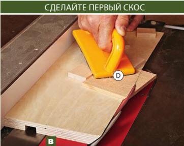 Прижимайте заготовку стенки D толкателем к несущей доске приспособления и упорам, опиливая первый скос.